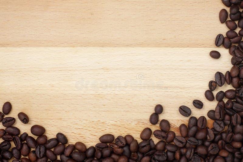Coffee beans border on wooden desk royalty free stock photos
