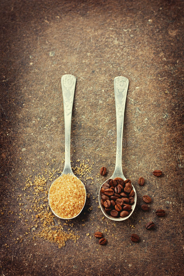 Coffee beans and brown sugar in a spoon royalty free stock images