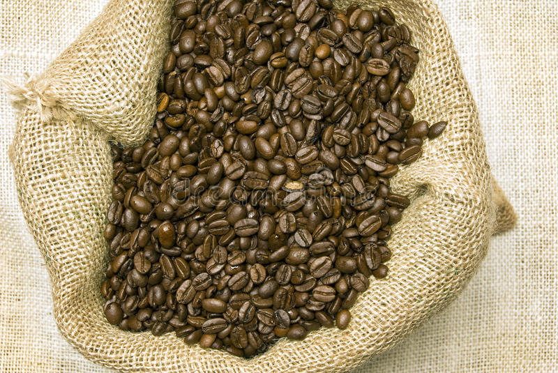 Coffee Beans In Burlap Bag Close Up. Horizontal shot of coffee beans in burlap bag shot overhead and close up royalty free stock photo