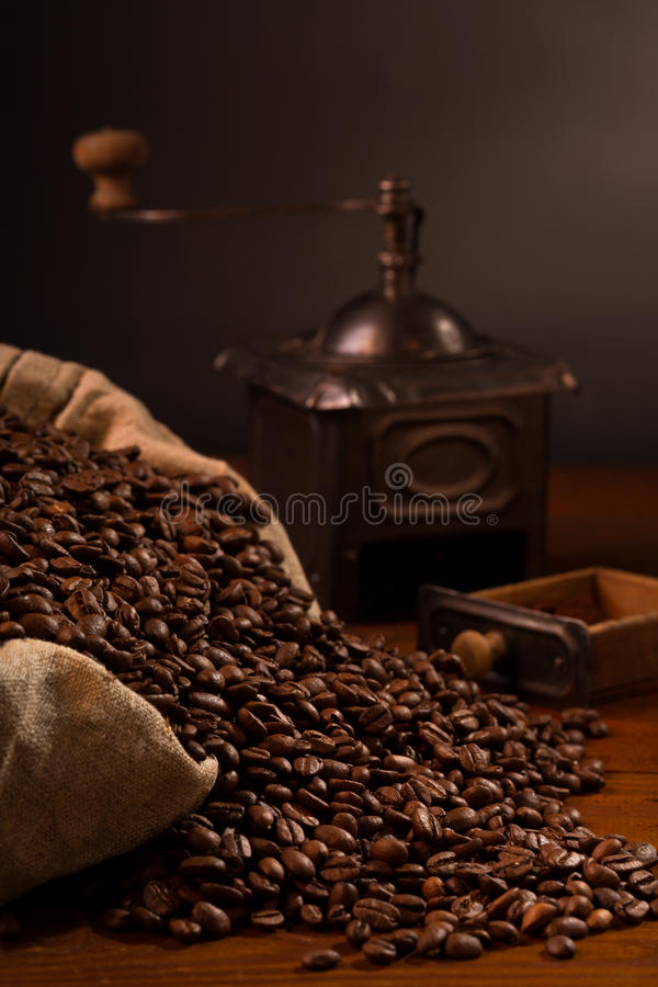 Coffee beans in burlap bag with old grinder royalty free stock photo