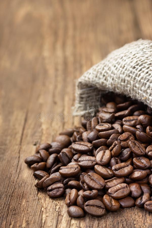 Coffee beans in burlap bag on wooden table royalty free stock photography