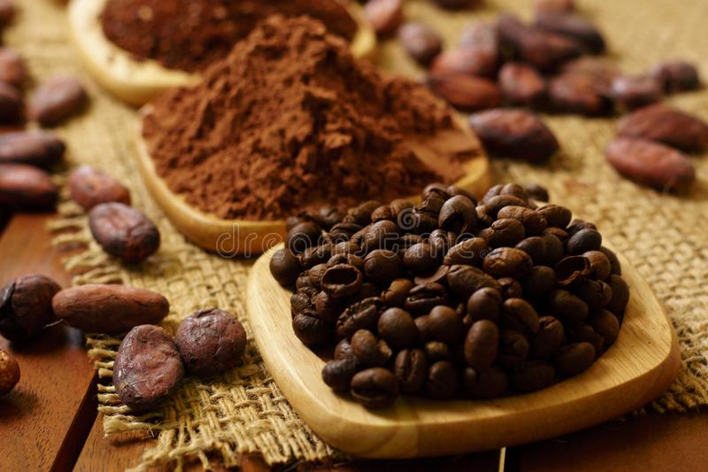 Coffee beans, cacao powder, cocoa nibs, on wooden plates on burlap. Background royalty free stock images