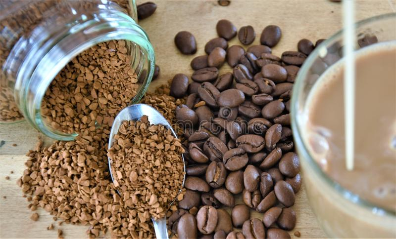 Coffee beans, a can of instant coffee and a coffee mug with milk royalty free stock photo