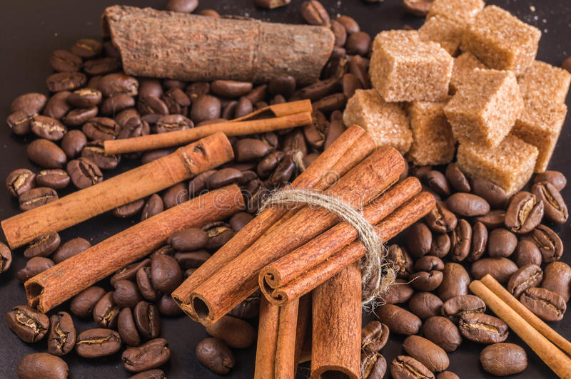 Coffee beans; cane sugar and cinnamon sticks. Coffee beans; cane sugar and cinnamon sticks on black background stock image