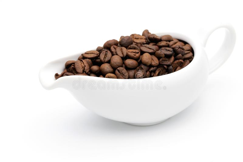 Coffee beans in a ceramic milk jug. On white background royalty free stock photos