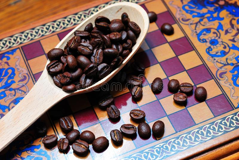 Coffee beans on a chessboard. Coffee fried grains in a wooden spoon on a chessboard royalty free stock images