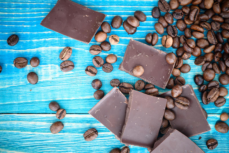 Coffee beans with chocolate glaze and dark chocolate on wooden background royalty free stock photo