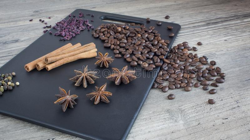 Coffee beans, cinnamon sticks and star anise. Spices and food on the wooden table. Ingredients for making coffee royalty free stock photography