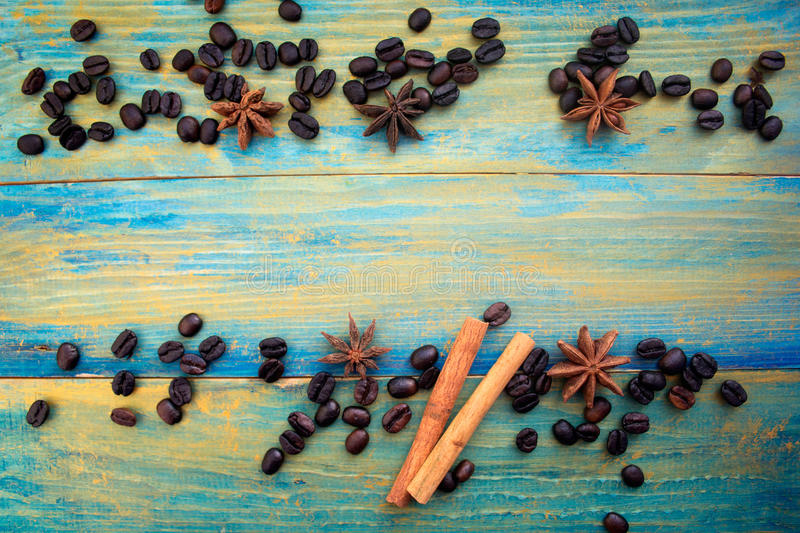 Coffee beans, cinnamon sticks and star anise on wooden background royalty free stock image