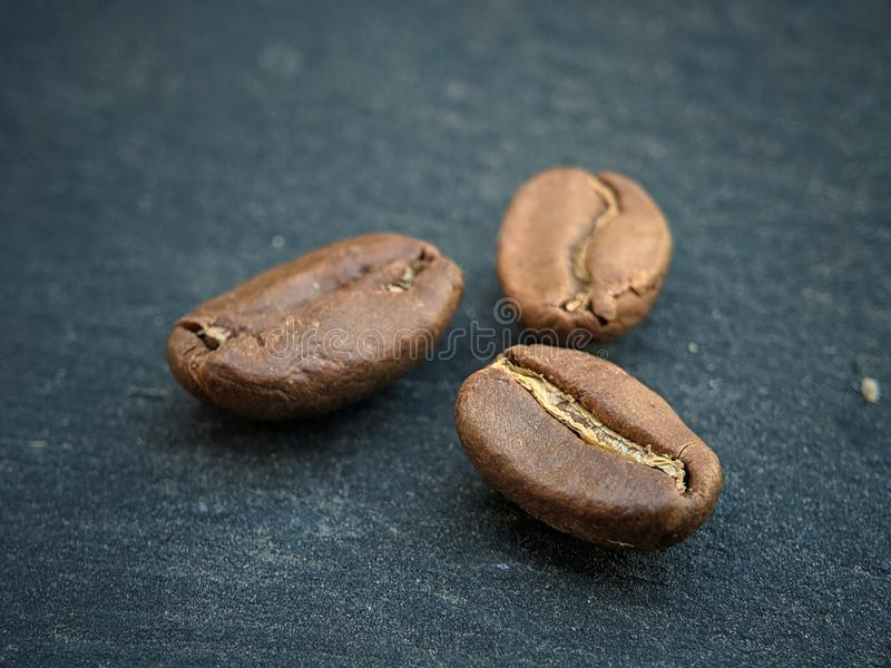 Coffee beans close up on black backdrop board royalty free stock photo