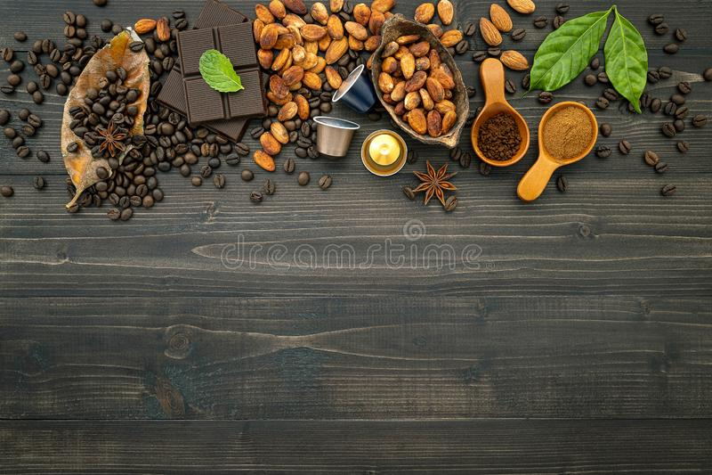 Coffee beans , cocoa beans ,coffee capsule ,dark chocolate bar and coffee powder on dark wooden background. Top view with copy royalty free stock photos