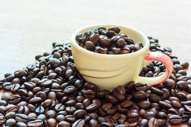 Coffee beans. Coffe beans on wood background with cup royalty free stock photo