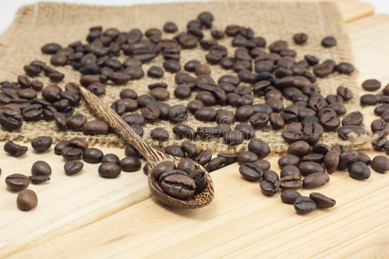 Coffee beans on a coffee spoon. Coffee beans on sackcloth and wood background, selective focus stock images