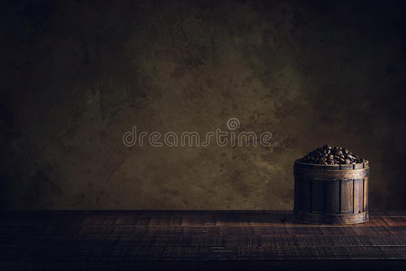 Coffee beans in container on wood floor and old paper vintage ag stock photo