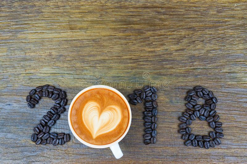 2018 coffee beans and a cup of coffee on wood stock image