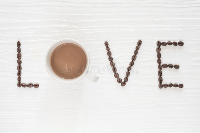 Coffee beans with cup of coffee on wooden table. stock photos