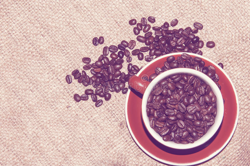 Coffee beans cup sack vintage filter. Coffee beans around a cup on the sack background through a vintage filter. Copyspace royalty free stock photos