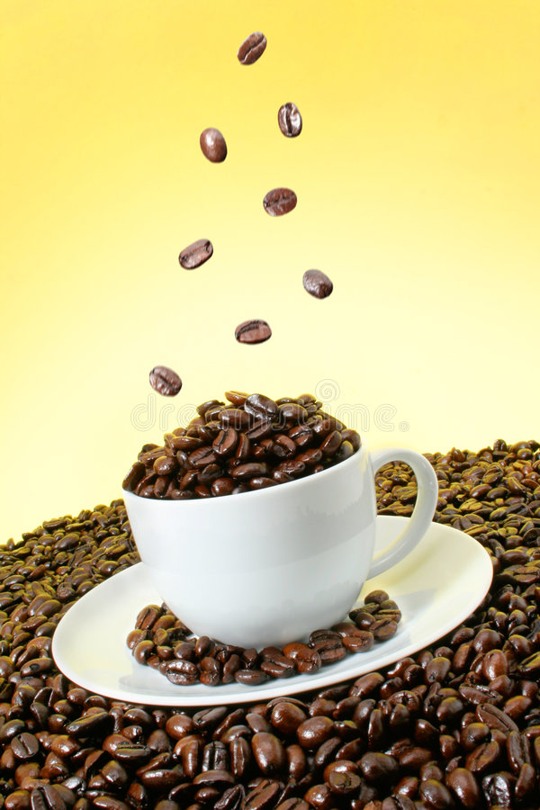 Coffee beans falling over a white cup