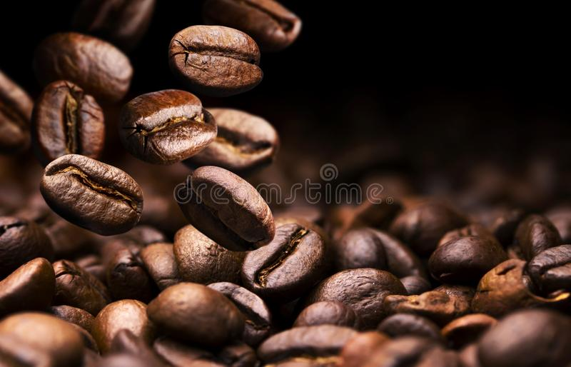 Coffee beans falling on pile, black background with copy space, close up stock photo