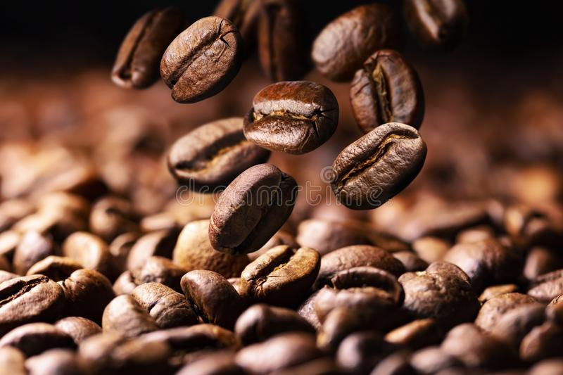 Coffee beans falling on pile, dark background with copy space, close up royalty free stock image