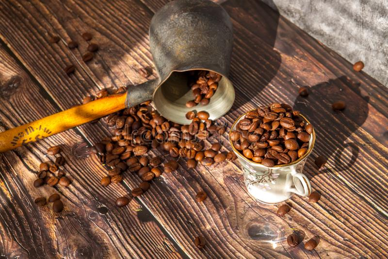 Coffee beans falling on wood table, vintage toned. How to choose a quality coffee. royalty free stock images