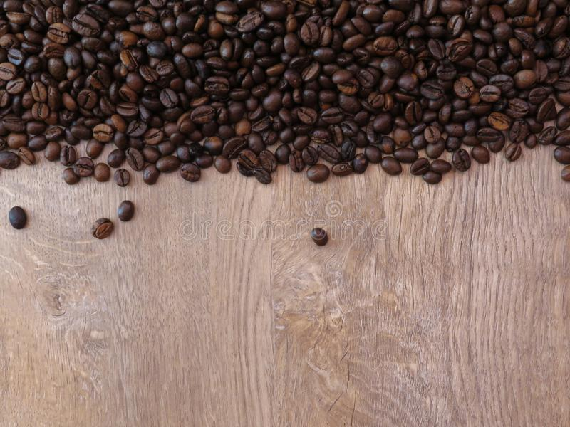 Coffee beans on fine oak tree wood texture pattern background. Space for text. stock photography