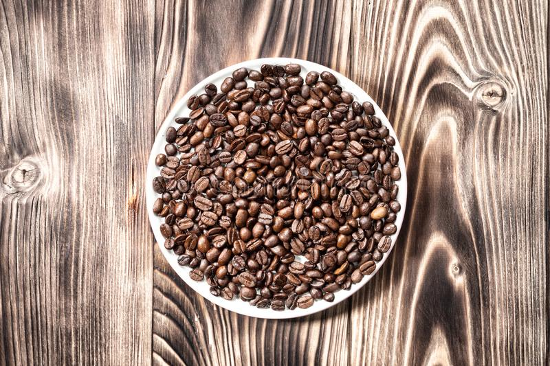 Coffee beans fresh roasted in round bowl on a wooden table royalty free stock image