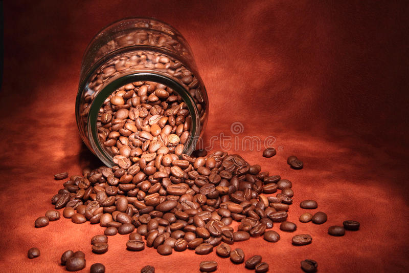 Coffee beans in a glass jar. Coffee beans spilling from a glass jar royalty free stock photos