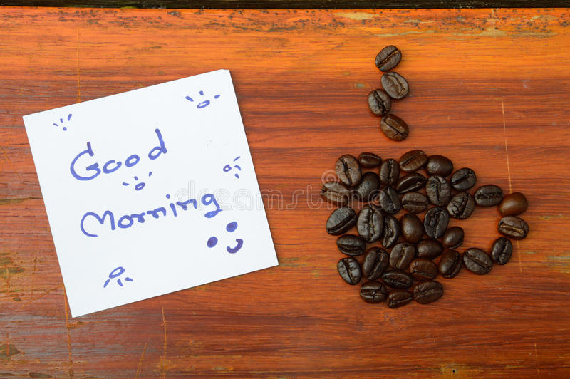 Coffee beans and good morning note. On the wooden background royalty free stock image