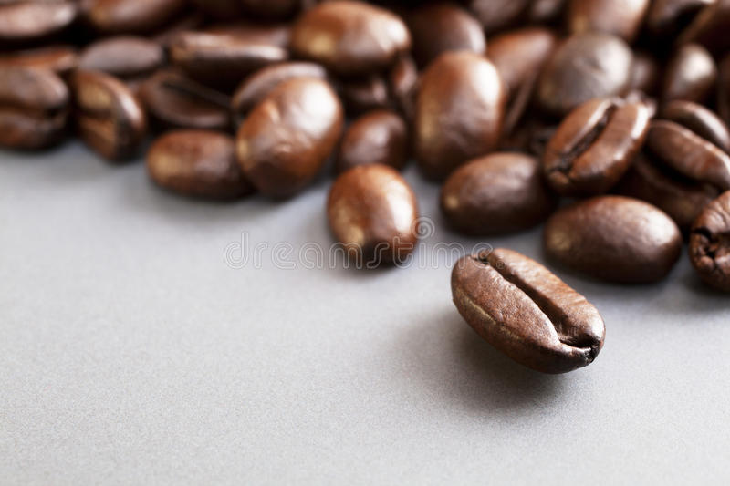 Coffee Beans on Grey. Fresh Italian roast coffee beans on a grey ceramic surface royalty free stock photography