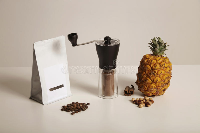 Coffee beans, grinder, pineapple, nuts and cinnamon royalty free stock photography