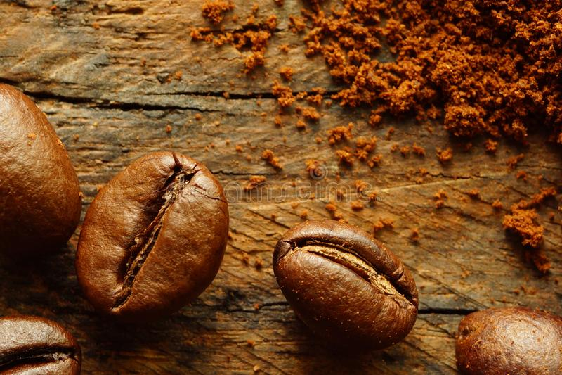 Coffee beans and ground coffee on rustic board. royalty free stock photo