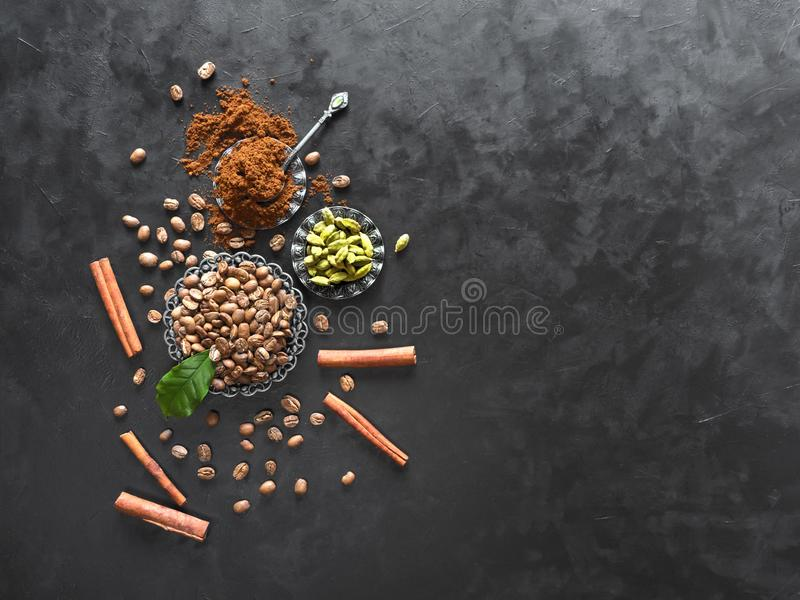 Coffee beans, ground powder, cinnamon and cardamom on black background. Top view with copy space stock photo