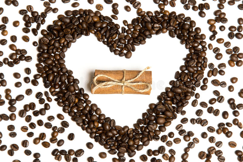 Coffee beans in heart shape and cinnamon in the center stock image