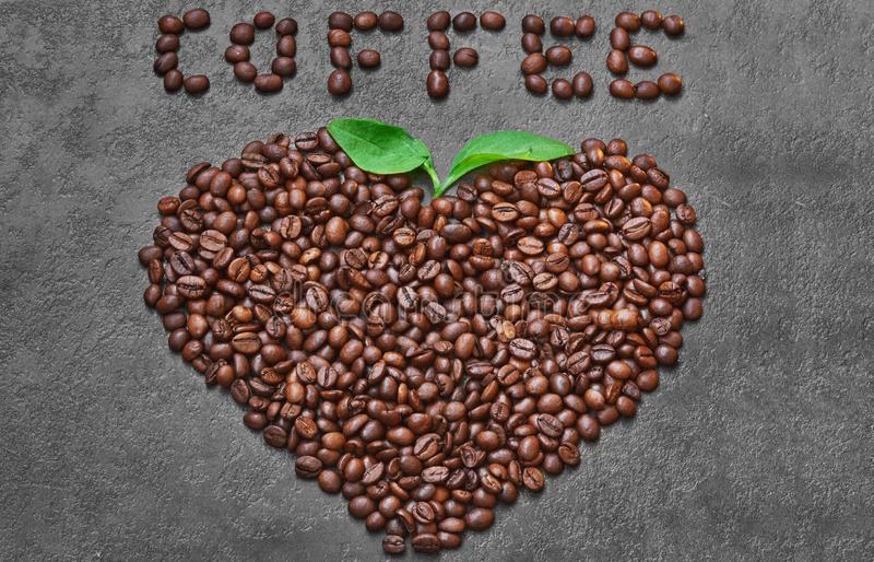 Coffee beans in heart shape with green leaves and coffee word on dark grey background.  royalty free stock photography