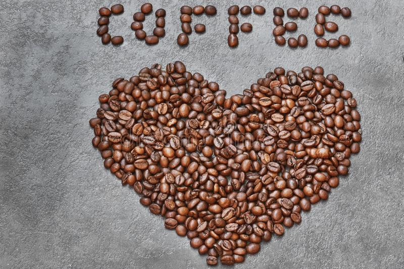 Coffee beans in heart shape with coffee word on top on dark stone table.  stock photography