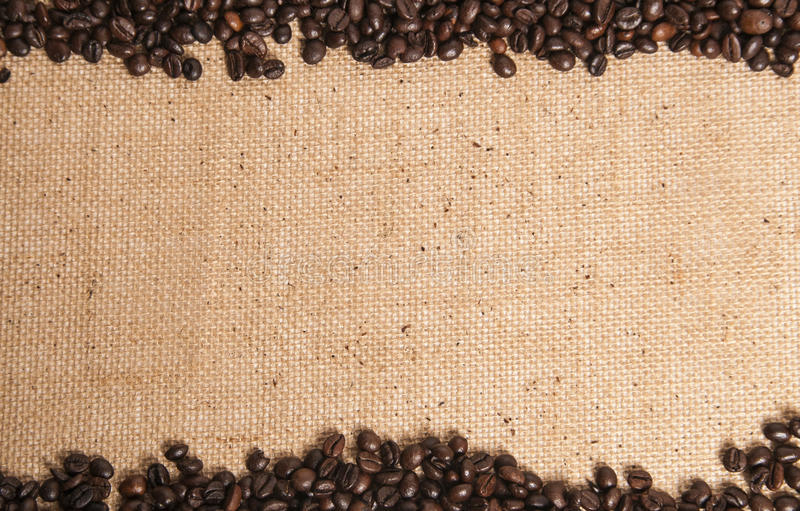 Coffee beans on hessian sack. Hessian sack with coffee bordering the top and bottom stock image