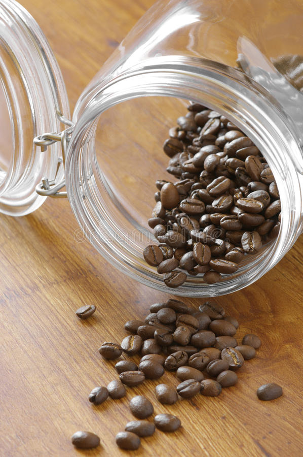Coffee beans in jar. Coffee beans overflowing from glass jar on wooden surface stock images