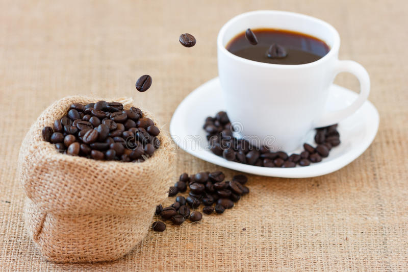 Coffee beans jumping into white cup royalty free stock photography
