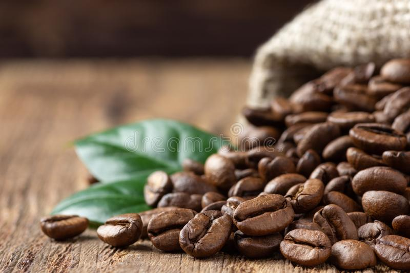 Coffee beans and leaf in burlap bag on wooden table.  stock images