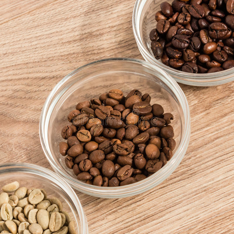 Coffee beans of medium roast in a glass bowl surrounded by green royalty free stock images