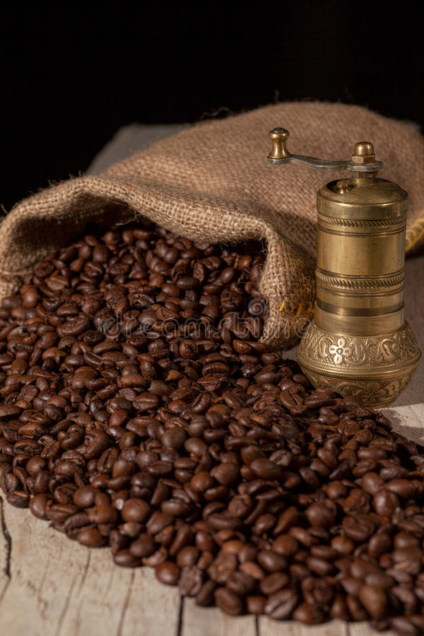 Coffee beans and old brass mill royalty free stock photo