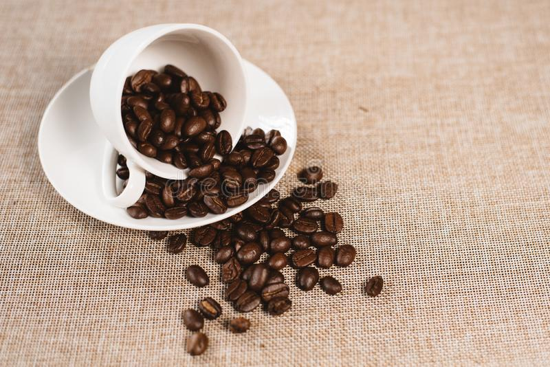 Coffee beans overflow on a white cup over a burlap sack royalty free stock photography