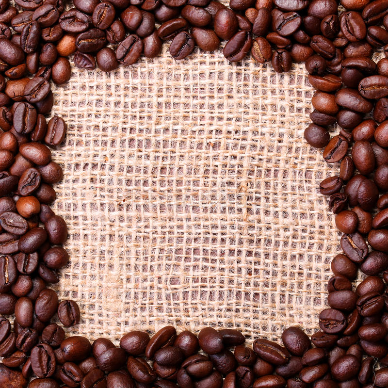Coffee Beans, placed in shape of frame on linen or burlap background royalty free stock photos
