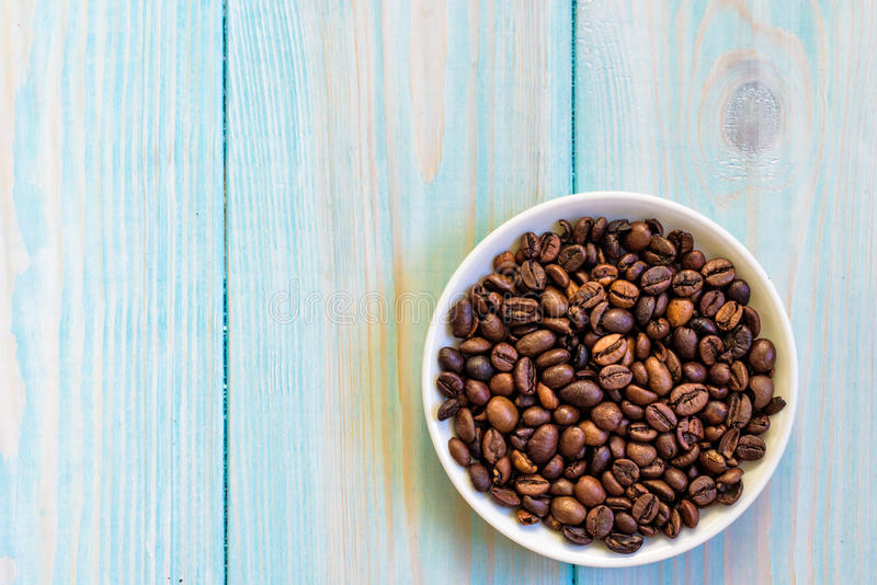 Coffee beans in plate. Flat lay on rustic light blue wooden background stock images