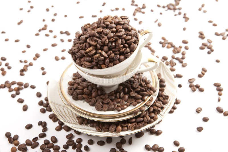 Coffee beans in porcelain cup on white background. Coffee beans inside old porcelain cup on white background royalty free stock images