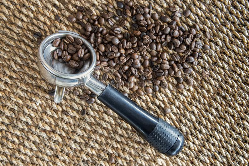 Coffee beans, portfilter, and water hyacinth wickerwork background.  royalty free stock photos