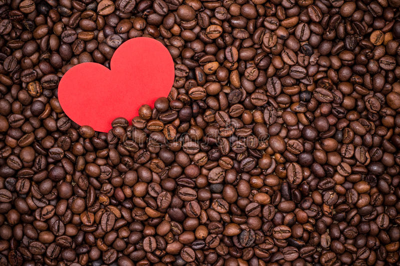 Coffee beans with red paper heart stock photos