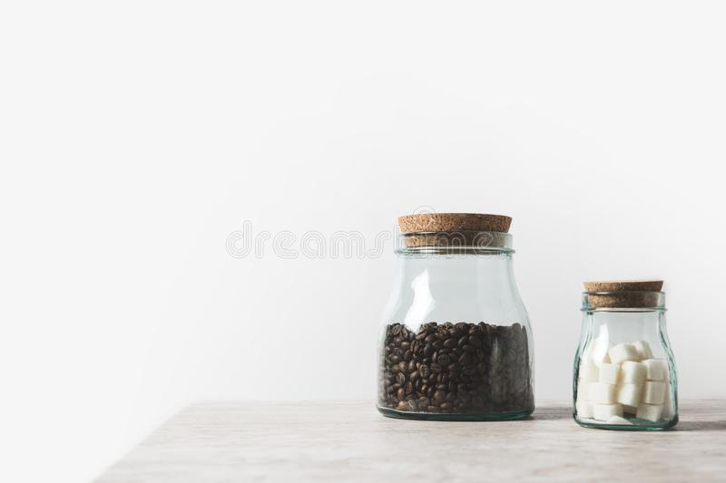 Coffee beans and refined sugar in glass bottles on marble table. On white royalty free stock photo