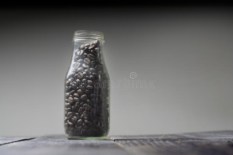 Coffee beans. Roasted coffee beans are stored in glass bottles without a bottle cap. Isolated shades of dark brown and vintages background caffeine cappuccino royalty free stock photos